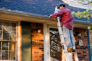 A man standing on a ladder ensuring the right roof maintenance for a house in Encino, CA